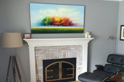 Click here to go to the Art page. Photograph of an original oil painting by George Peebles hanging on a gray wall over a brick fireplace with white mantle. Eames chair and tripod floor lamp on either side of the fireplace.